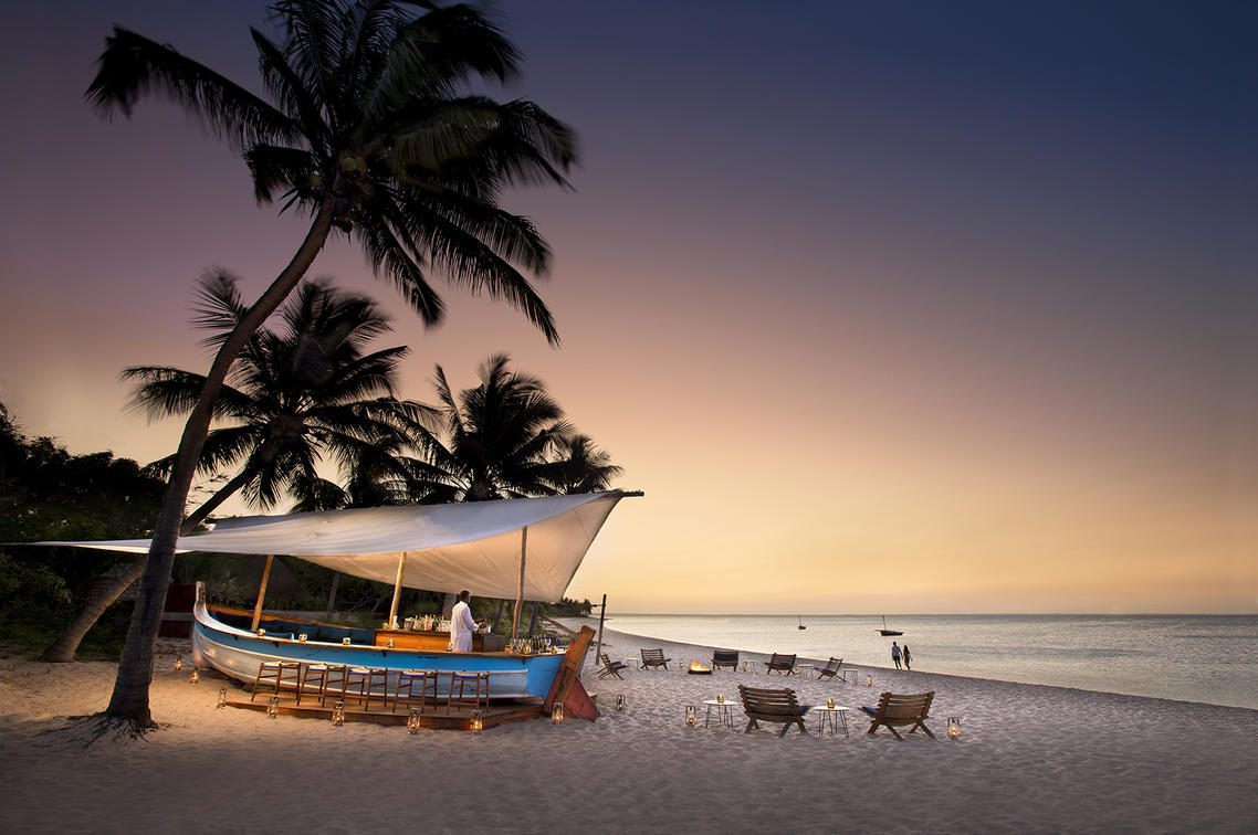 white sand beach with a boat shaped bar and chairs set up at sunset