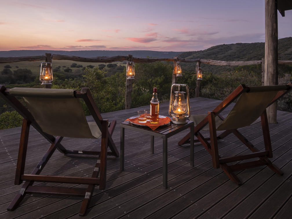 two deck chairs with lanterns at sunset seen on South Africa safari