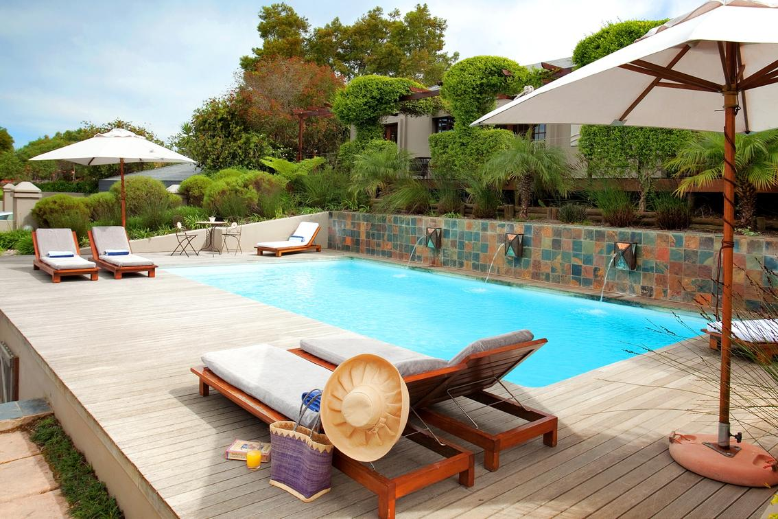 on this South Africa safari enjoy this pool with lounge chairs on deck and umbrellas
