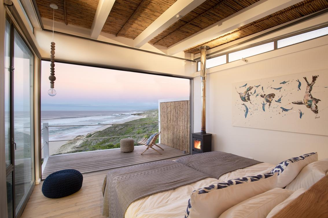 view from a bed with ocean in distance at sunset