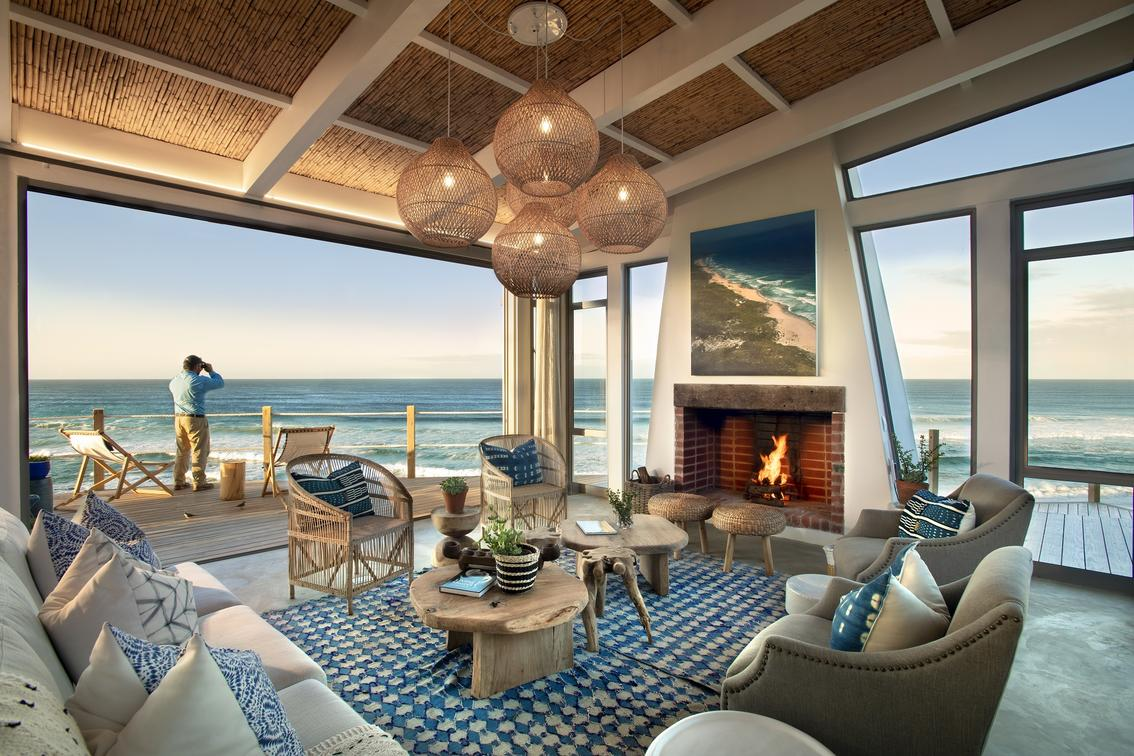 open room with couches, chairs and tables with ocean views overlooking the water at lekkerwater lounge