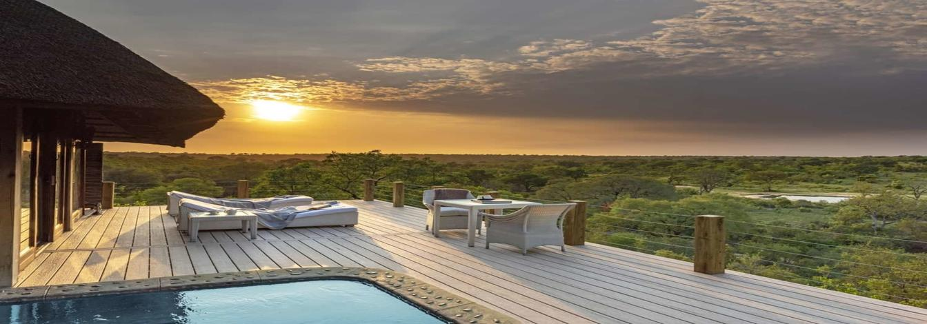 on this luxury South Africa safari enjoy deck with pool and lounge chairs overlooking large grassy area at sunset
