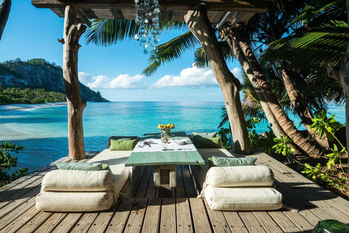 two lounge chairs and a table with palm trees and turquoise water