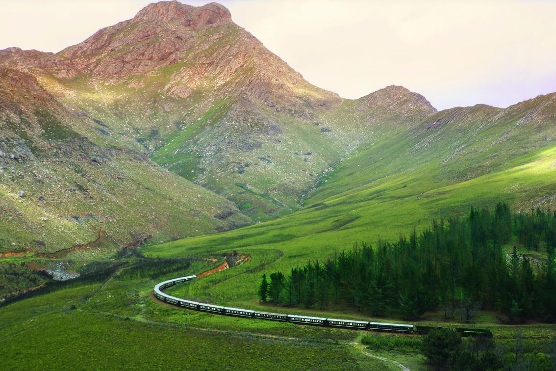 train track going through green fields with mountain landscape on this Africa train safari