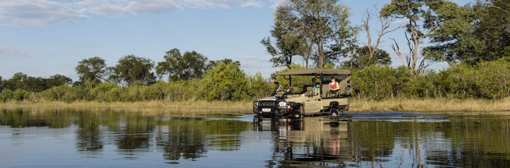 vehicle driving through water in khwai private game reserve