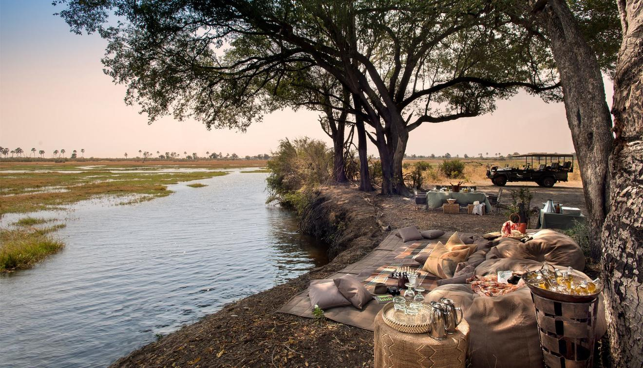 river and tree with a picnic blanket and drinks set up on this luxury Southern Africa safari