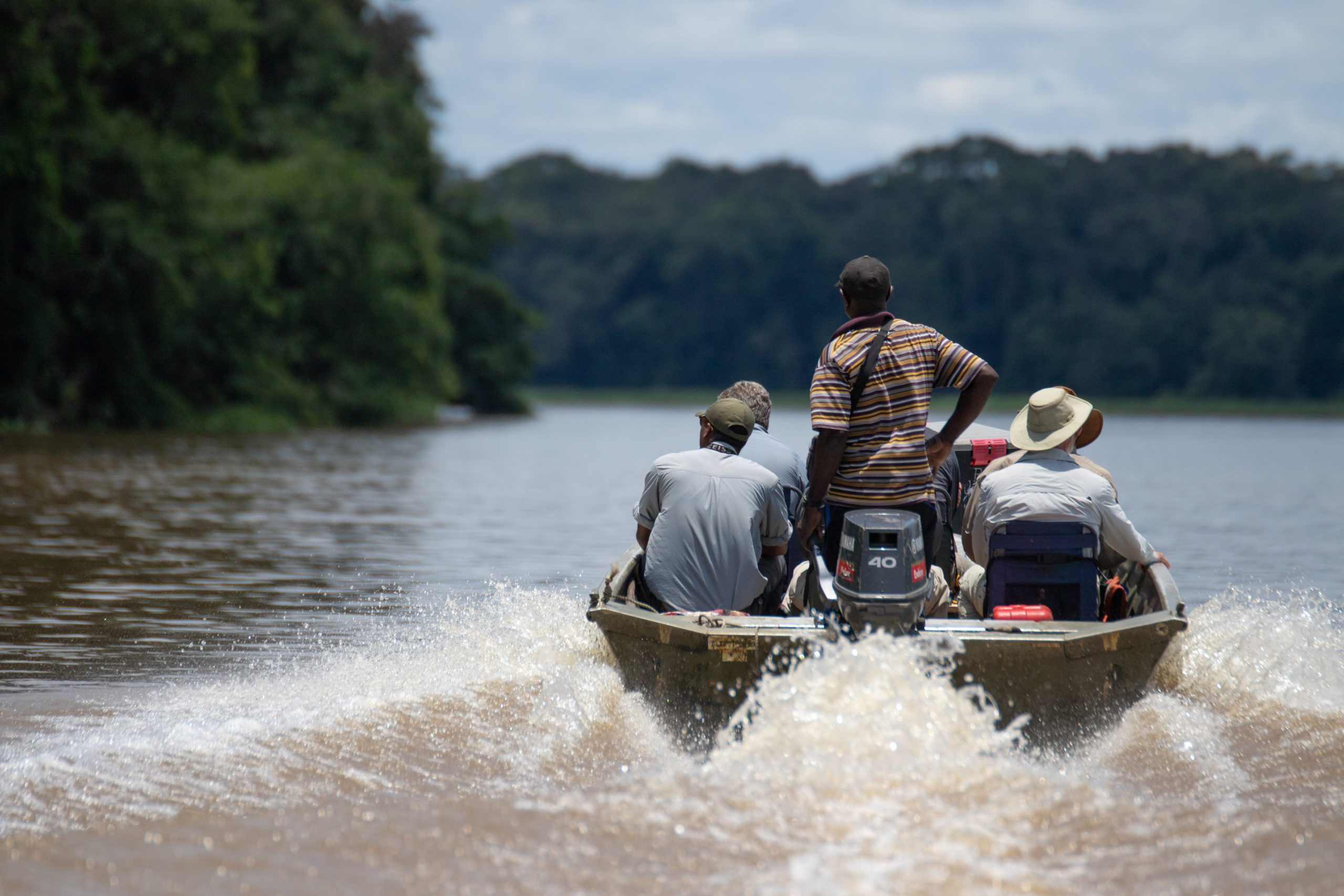 Sangha Lodge Congo Basin safari Odzala guests and guide cruising down river in small motor boat