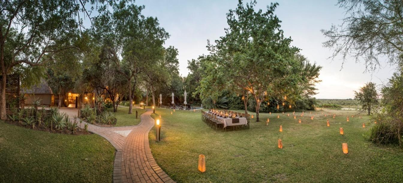 grassy area with a path and lantern lit dining area on this Cape Town and the Best of South Africa Safari