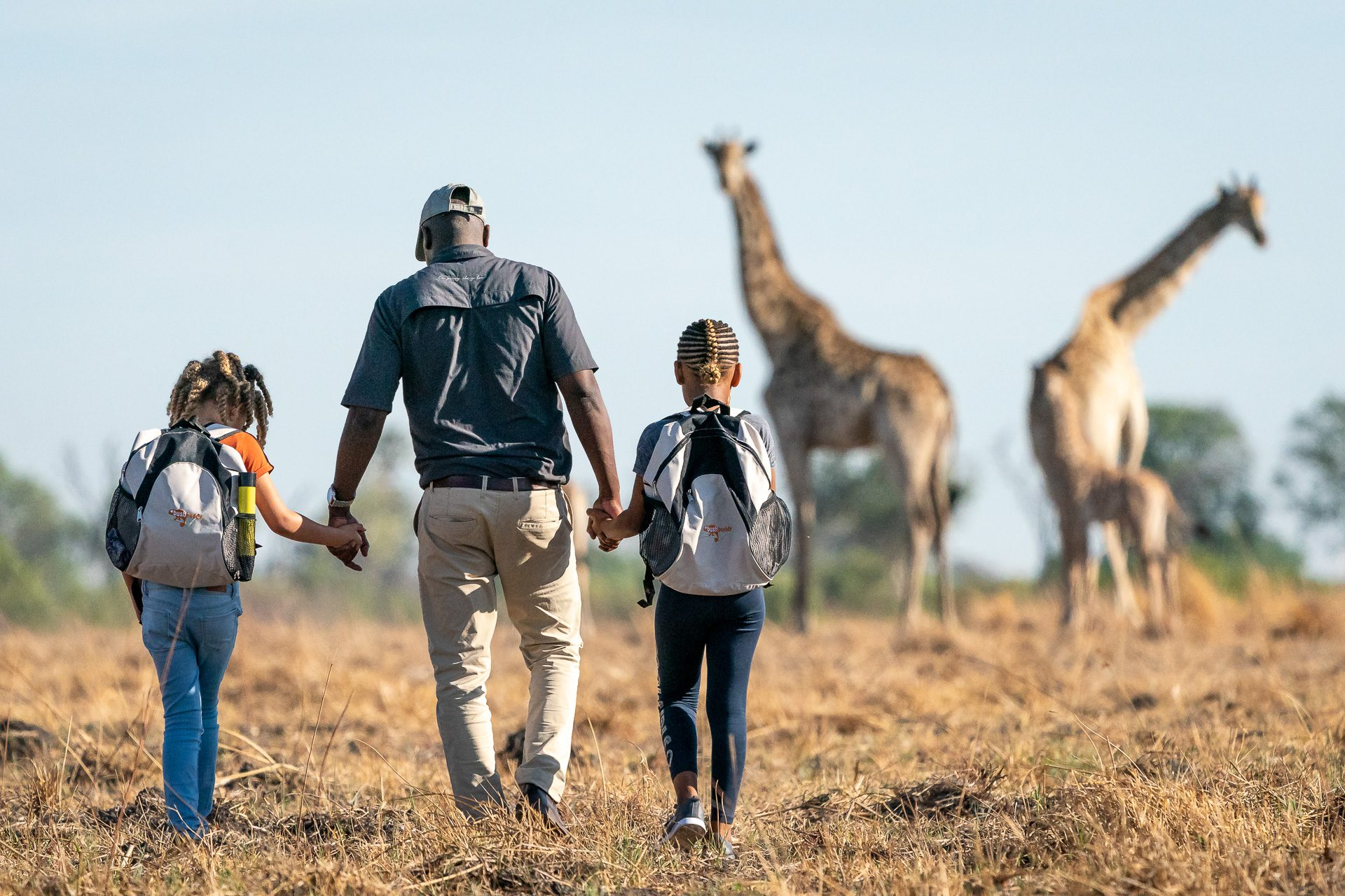 seba camp bush walk guide with two children on the best botswana safari. Family travel activities