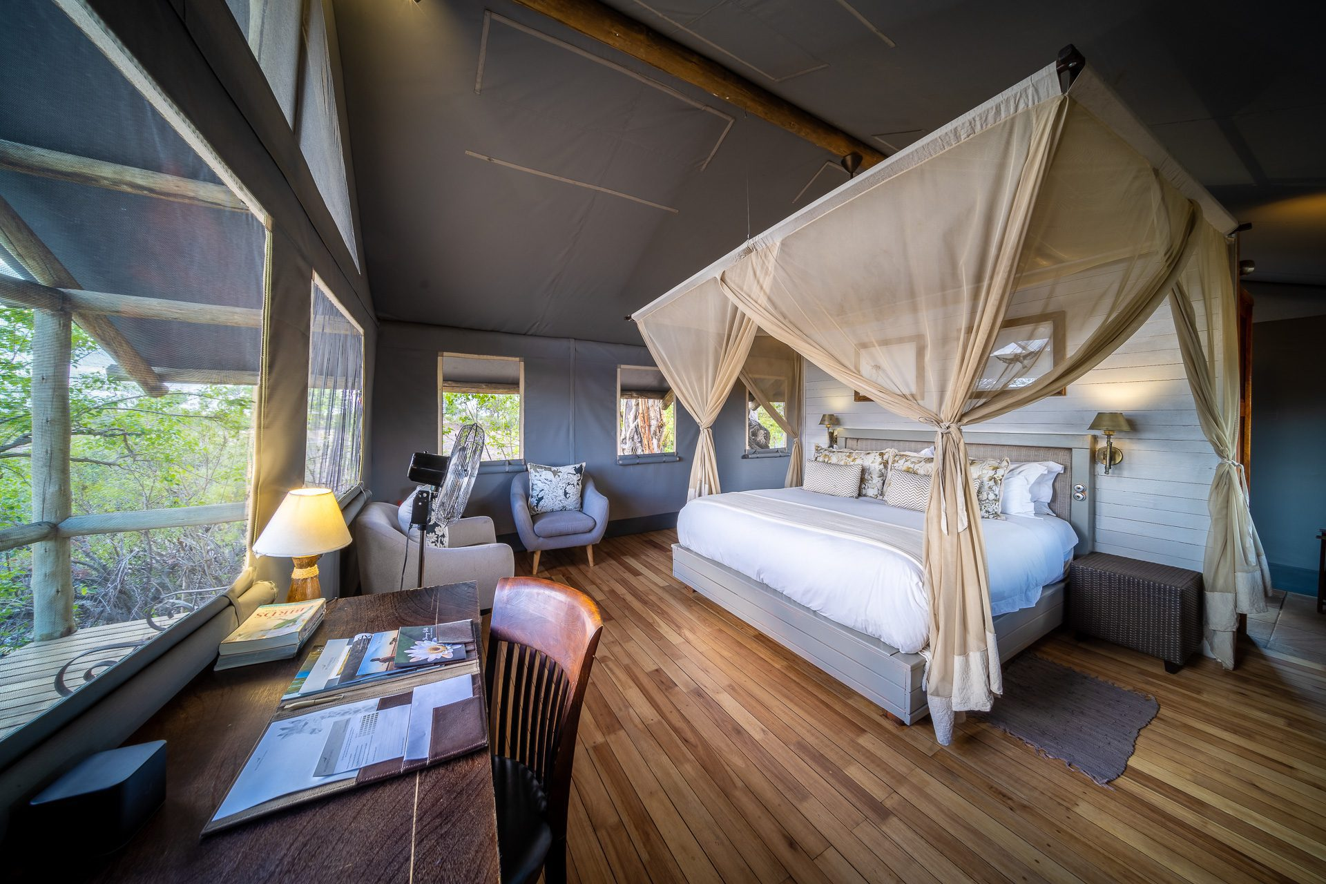 stay at seba camp interior room view of bed with nets drawn back on our off-grid Botswana safari