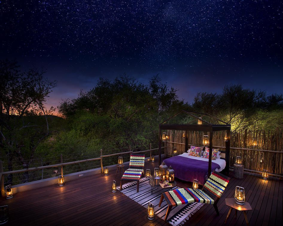 lanterns lit around a bed with two lounge chairs with starry sky