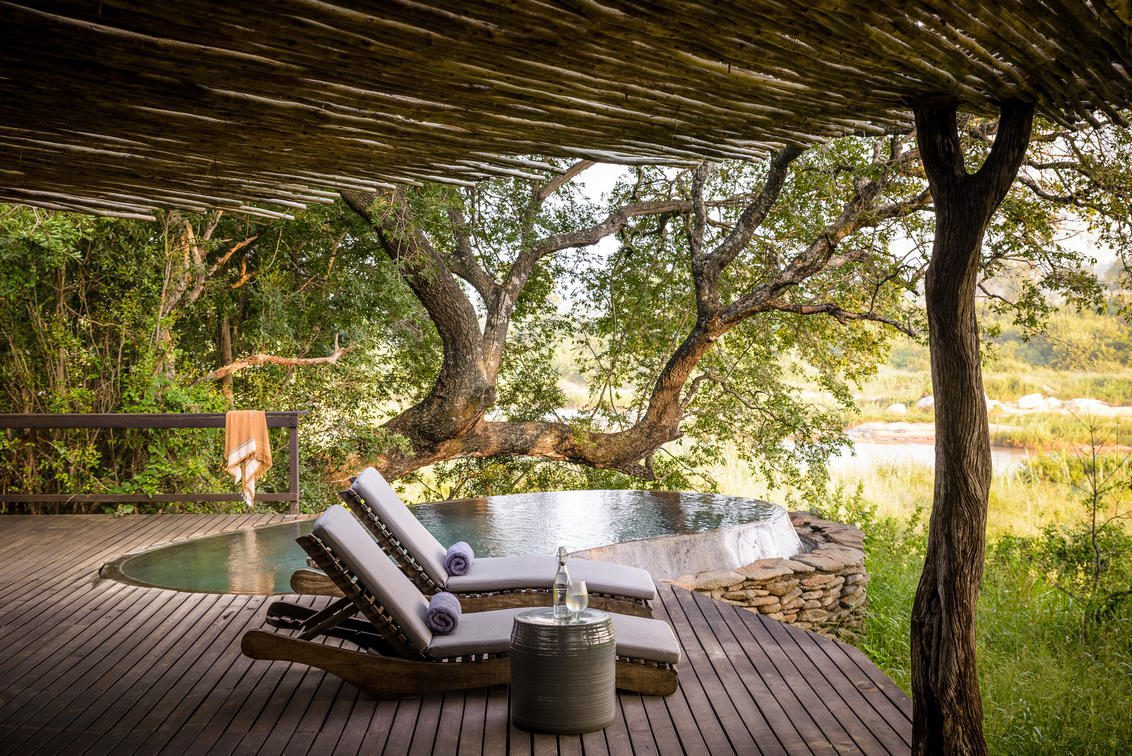 two chairs on a deck with a plunge pool looking out to the grass on our luxury safari in South Africa