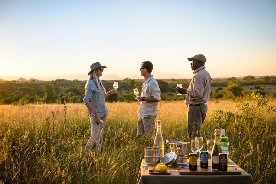 three people holding wineglasses with a table and bar setup on a grassy field