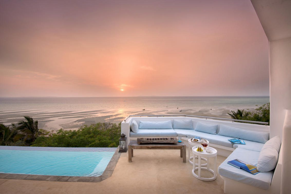 plunge pool and lounge chairs set up on a deck overlooking the ocean at sunset on Southern Africa romantic safari