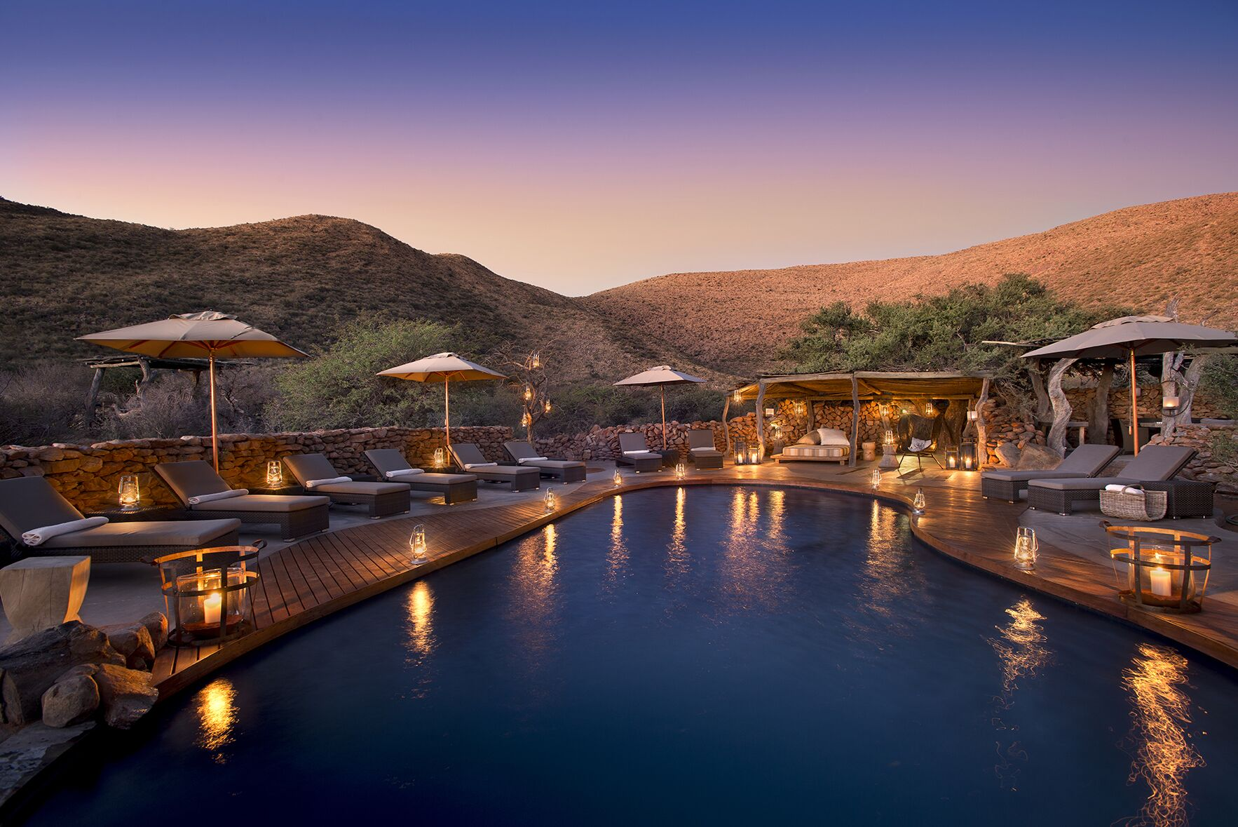 lantern lit pool at sunset with chairs around the deck and hills in the background
