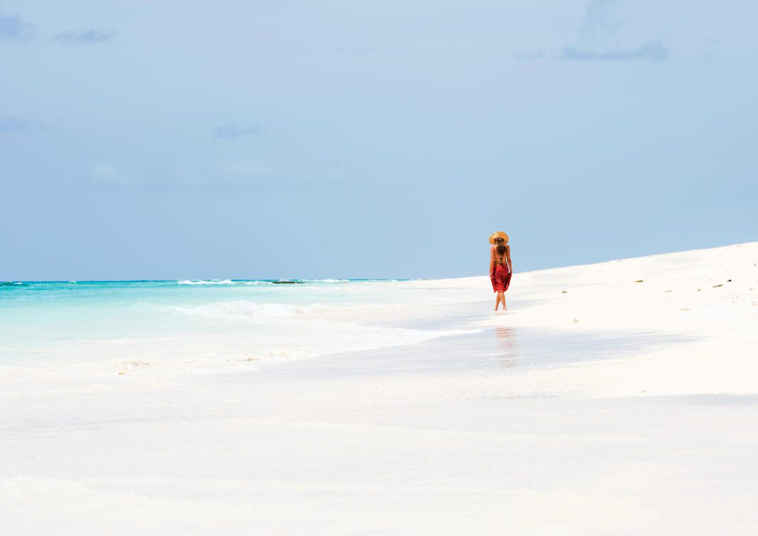woman walking on white sand beach with turquoise water