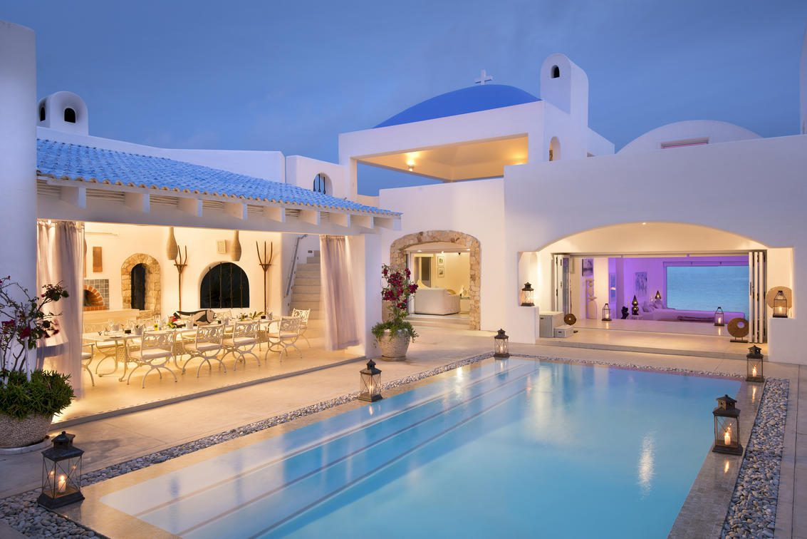 pool lit up at night with white building