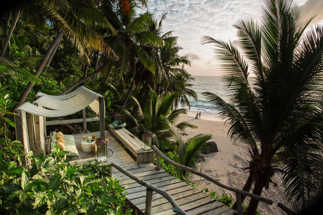 steps leading down to a deck with lounge chairs overlooking a beach with palm trees and the ocean