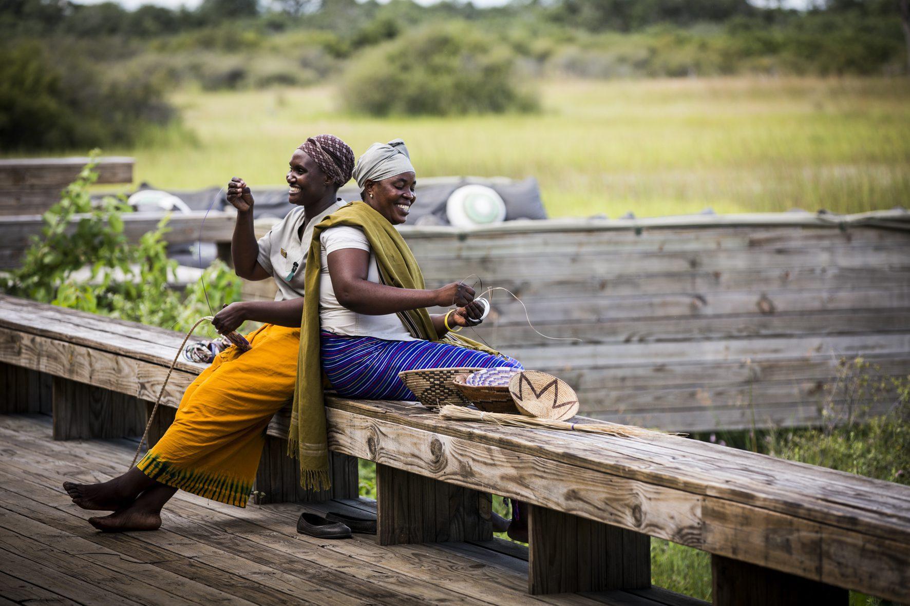 locals laughing and sitting on a bench vumbura plains botswana