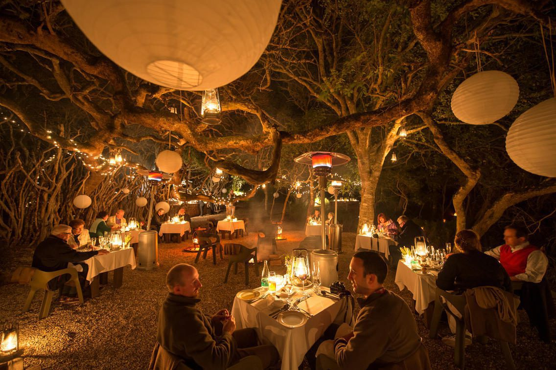 lantern lit grove with dining tables set up