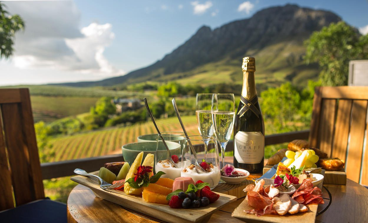 platter of cheese, meat and wine with vineyard views in the background on this Africa honeymoon safari