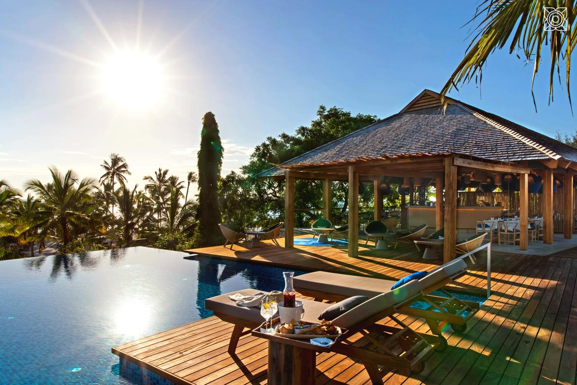 pool with lounge chairs on the deck and a bungalow on Southern Africa safari