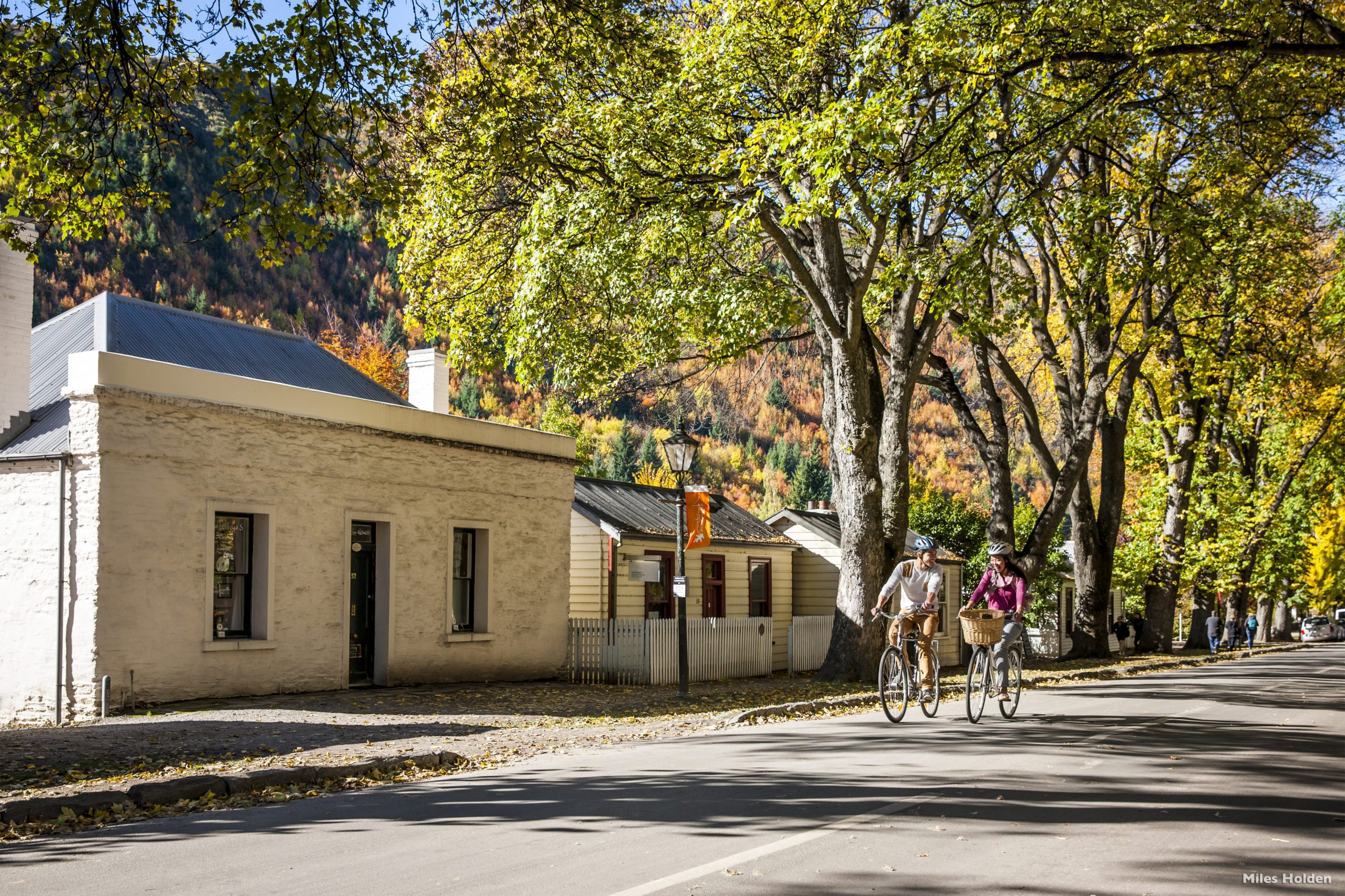 People biking through historic Arrowtown past a charming old building on a tree-lined street.