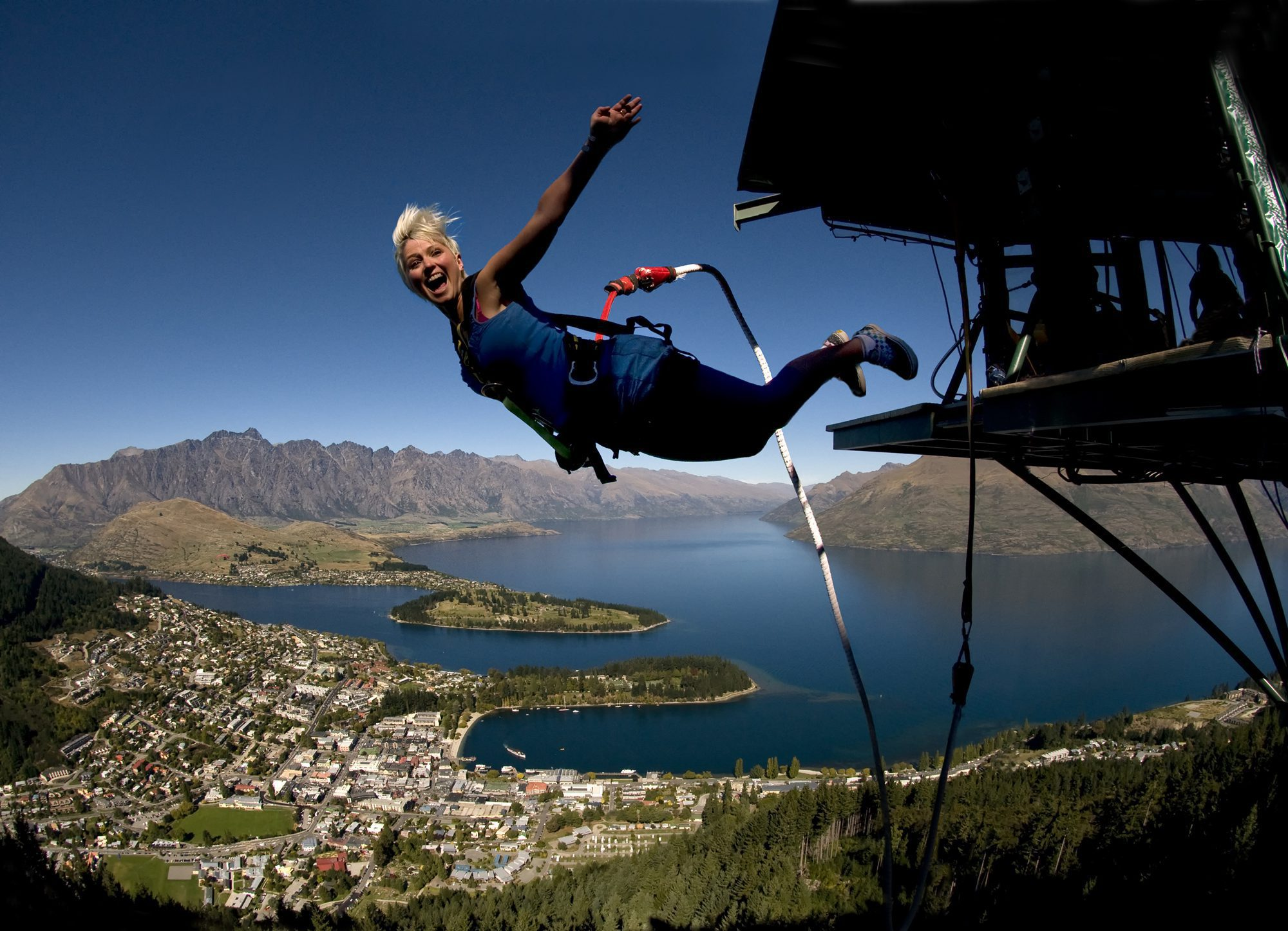 Woman looks at the camera as she bungee jumps off the platform in Queenstown