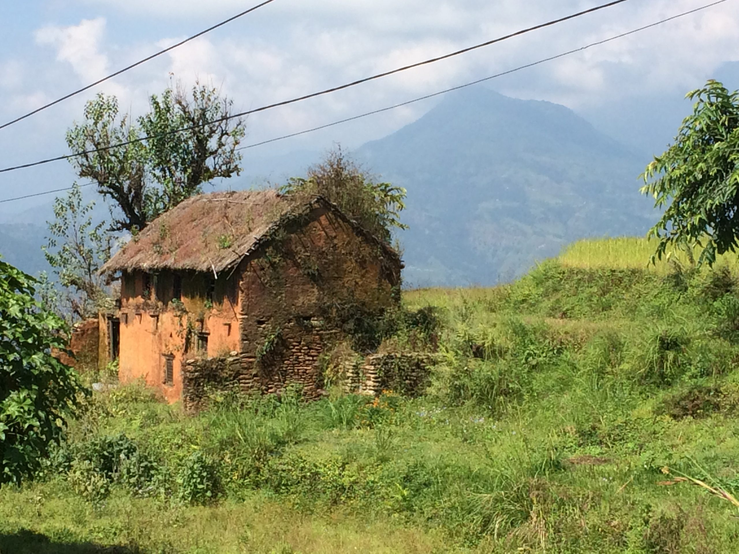 small house on nthe hillside with the mountains in the background