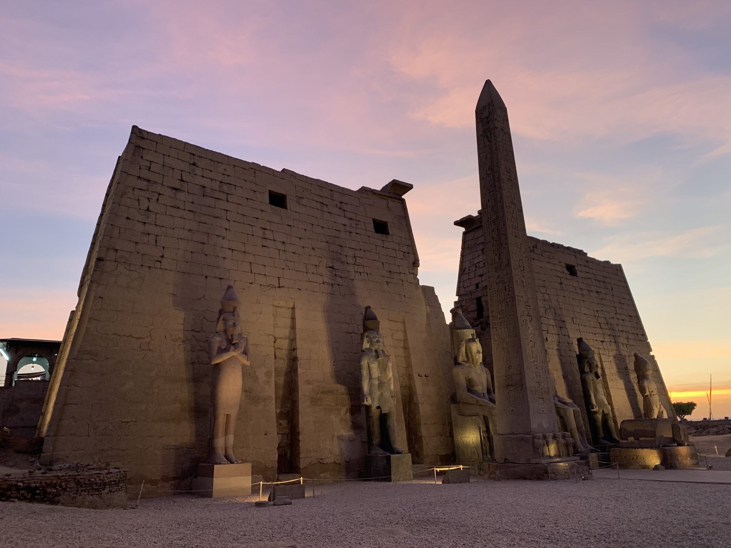 Luxor temple column and statues at sunset