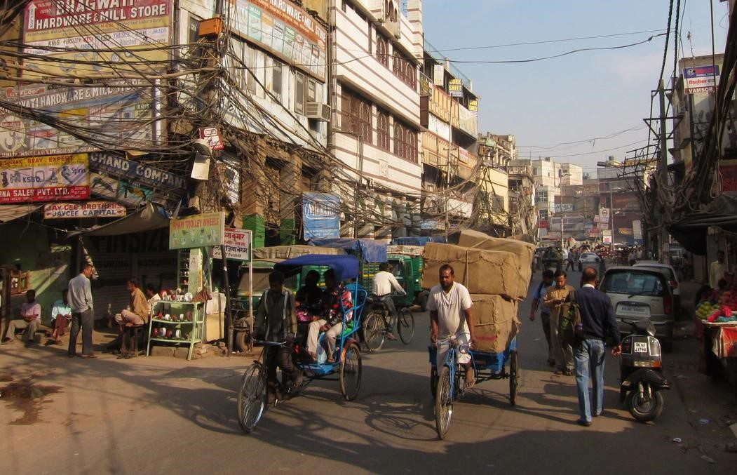 chaos of phone wires, people pulling carts, and rickshaws on a narrow dirt road