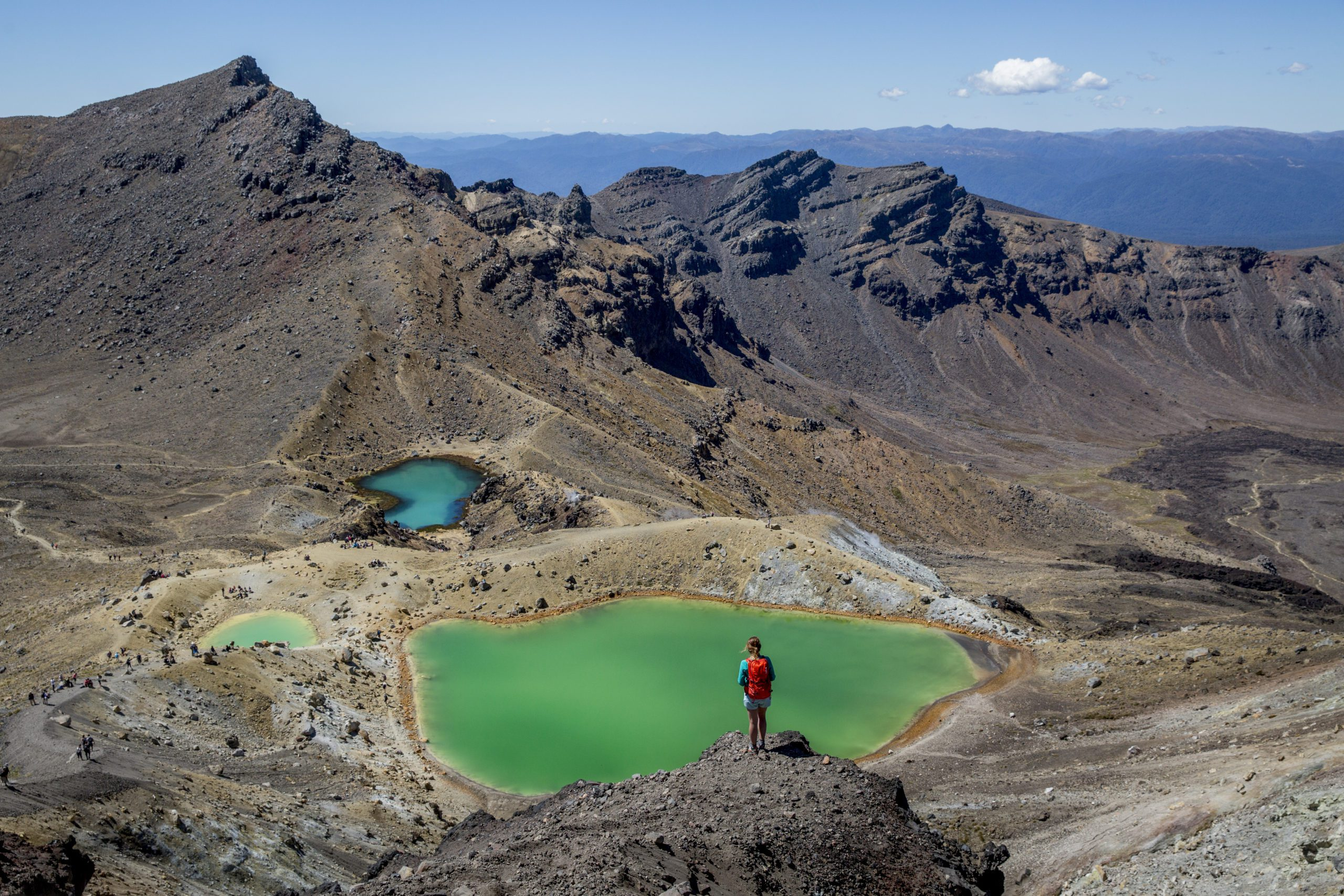 A hiker stops to admire the green lake on the Tongariro Alpine Crossing