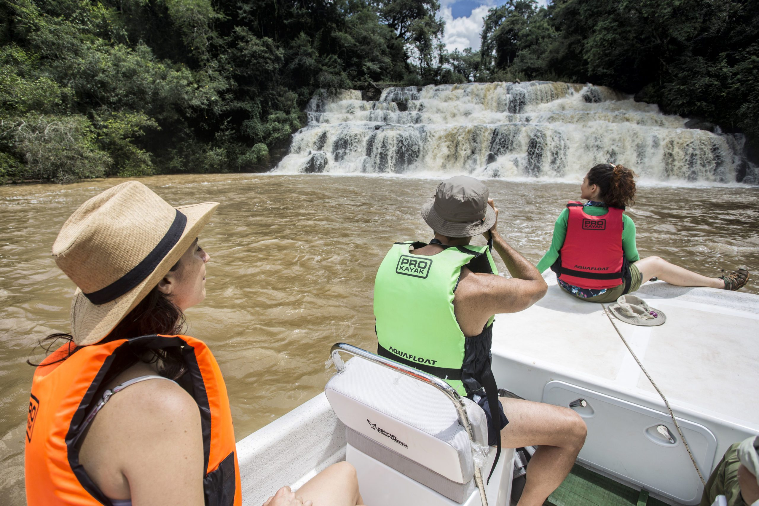 three people on a boat taking photos of Iguazu Waterfall