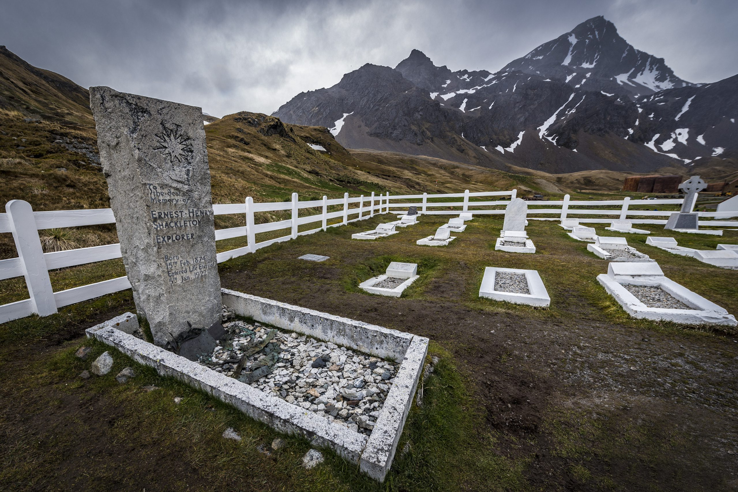 the tomb of explorer Ernest Shackleton in a small graveyard with mountains in the background