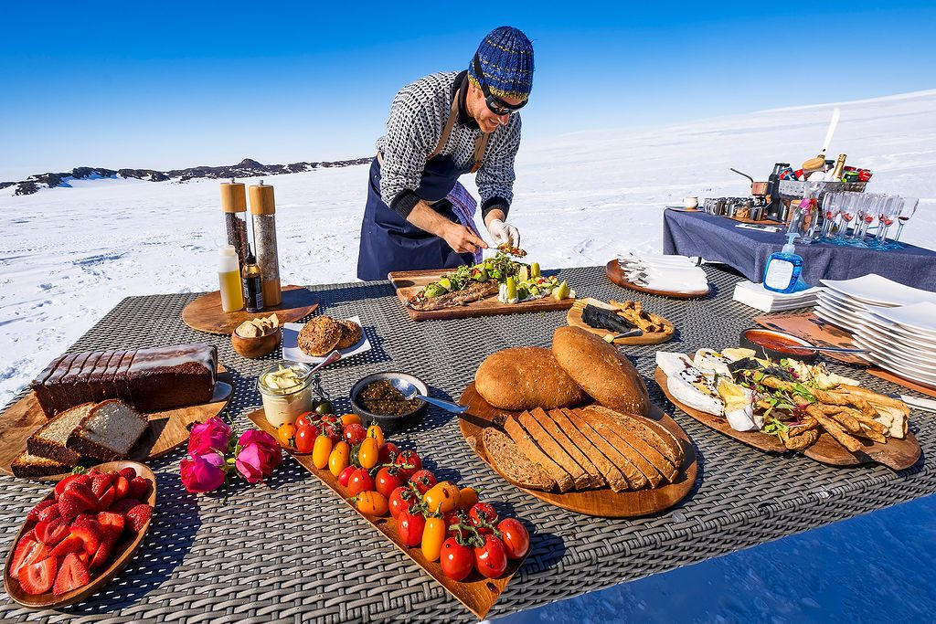 chef putting the finishing touches on his fresh picnic spread in Antarctica