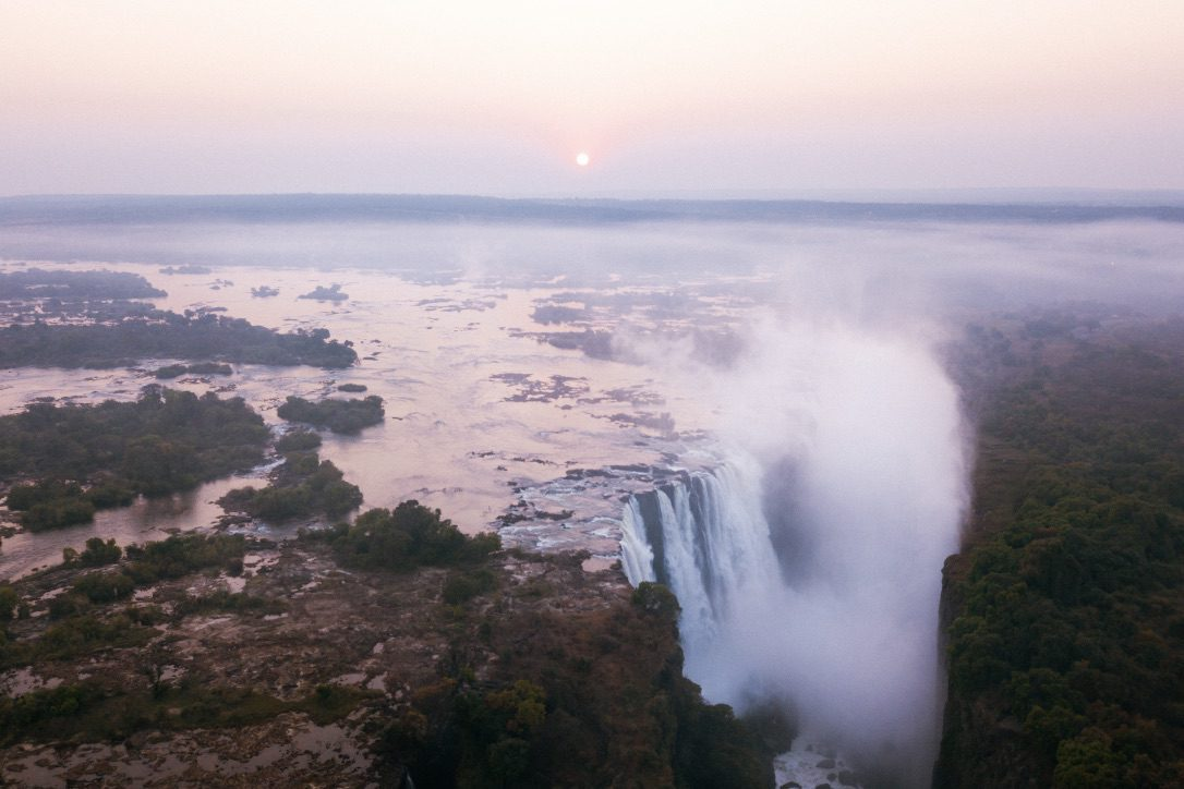 victoria falls from above with mist coming off of the falls