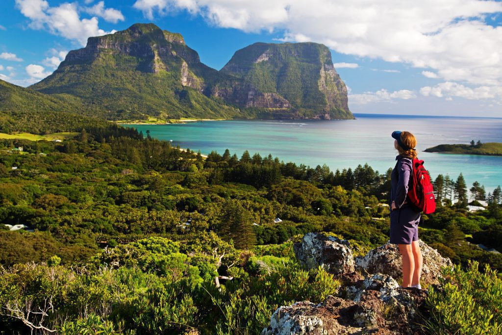 A lone hiker on Lord Howe Islands stops to admire the views of the beautiful mountains jutting out of the clear blue water.