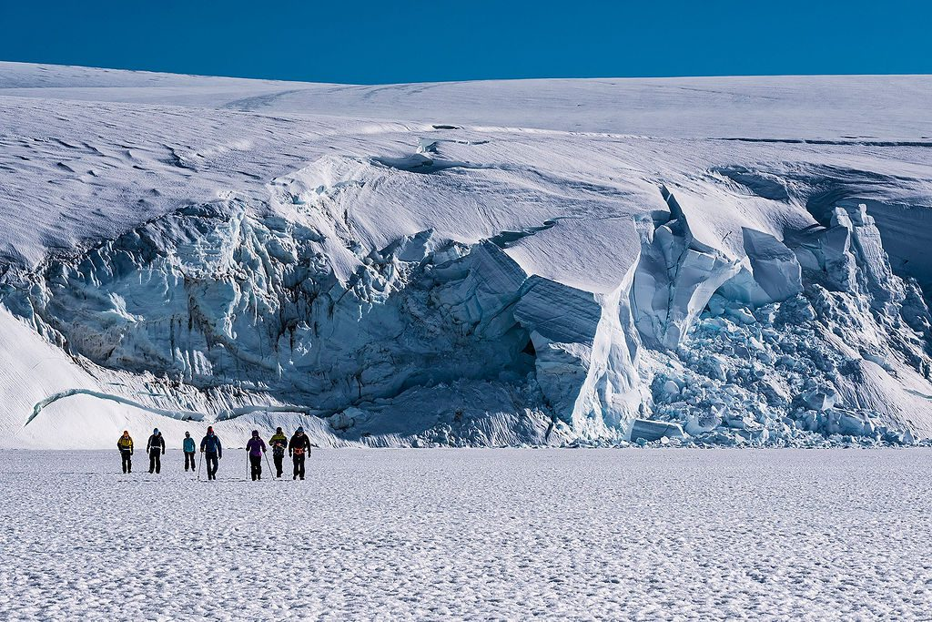 guests hiking along the ice in front of a glacier in Antarctica