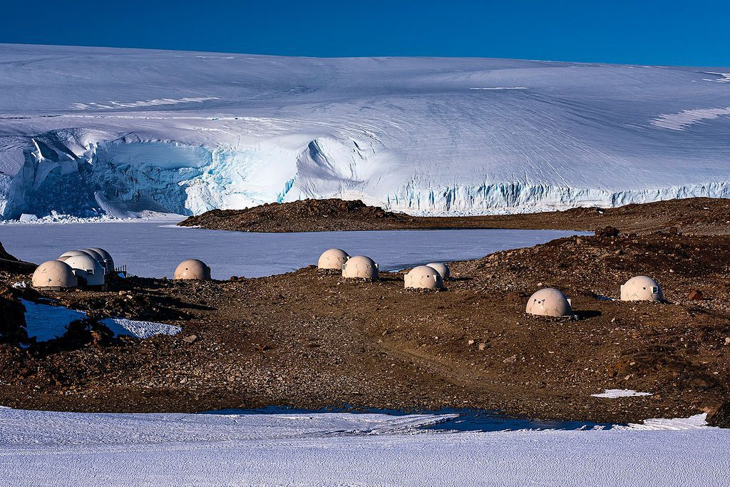 dome pods of Whichaway Camp dotted along the rocky terrain at the edge of a white glacier