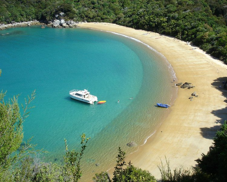A boat anchored in a sandy bay in Abel Tasman National Park with some kayaks