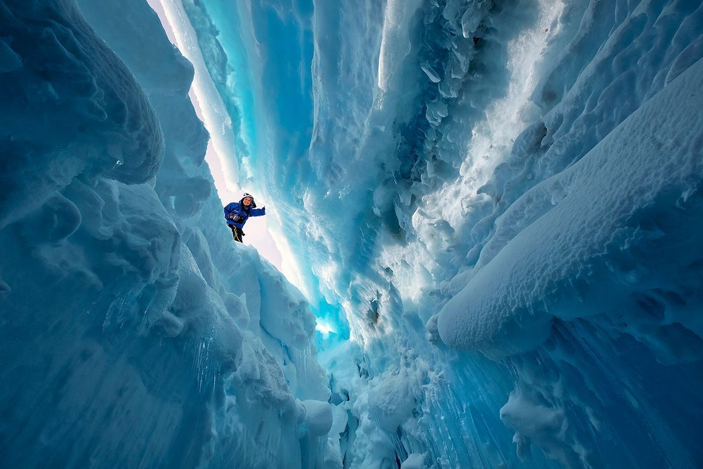 guest peaking into the aqua ice caves in Antarctica