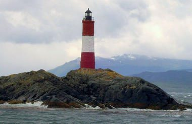 lighthouse sitting on a solitary island in the middle of the chilean fjords