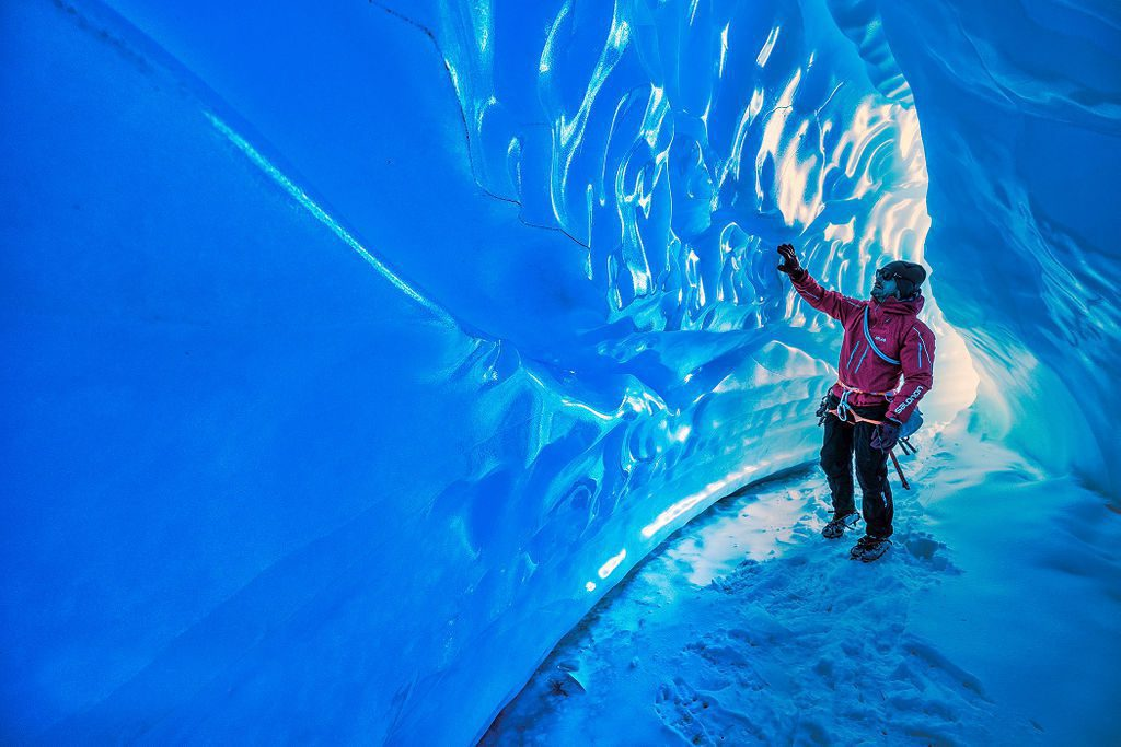 guest running a hand along the aquamarine ice cave in Antarctica