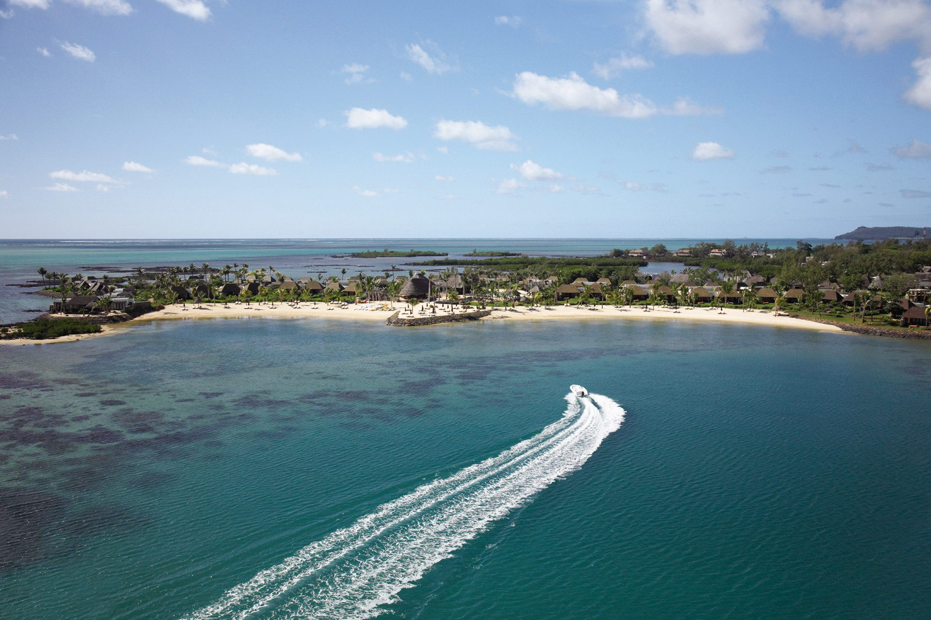boat with wake entering bay with sandy beach on safari in Mauritius