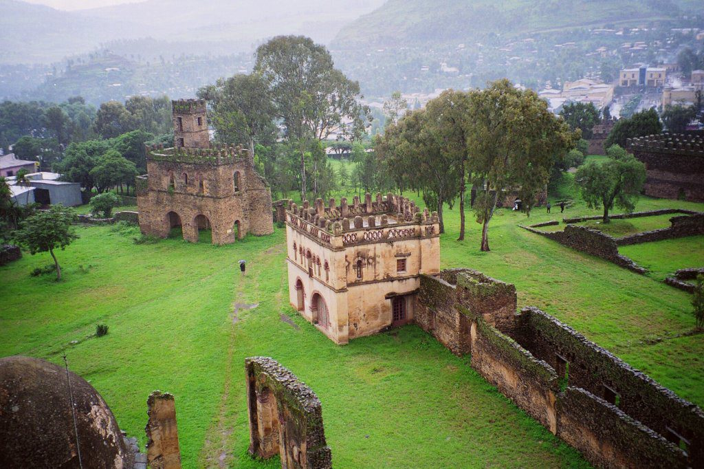 colorful green grass surrounding the brown Fasil Castle in Gondar Ethiopia