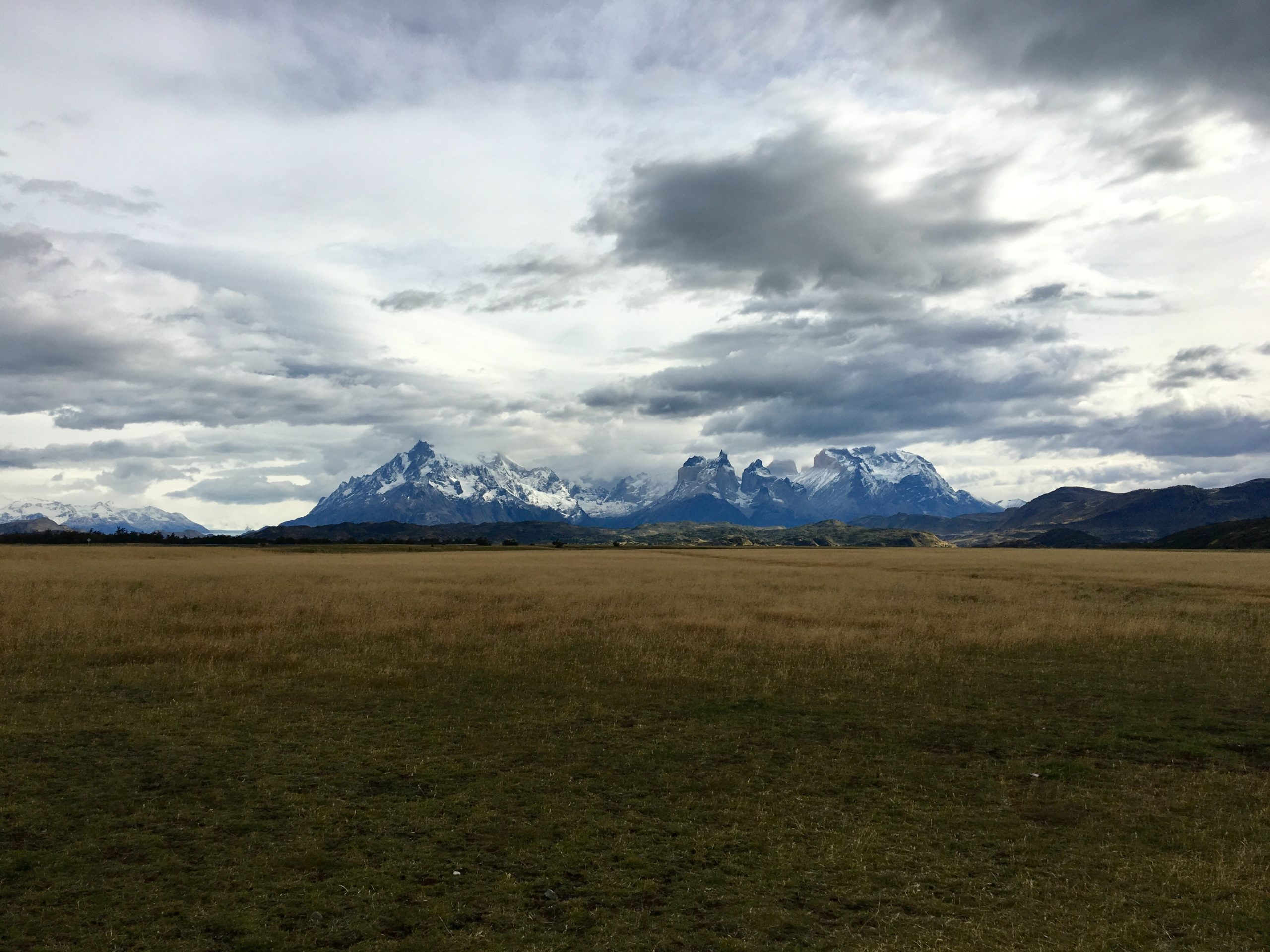 cloudy skies over Torres del Paine and an open field on this breathtaking Chile trip