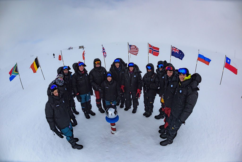 guests bundled up and gathered around the marker at the South Pole with country flags encircling them
