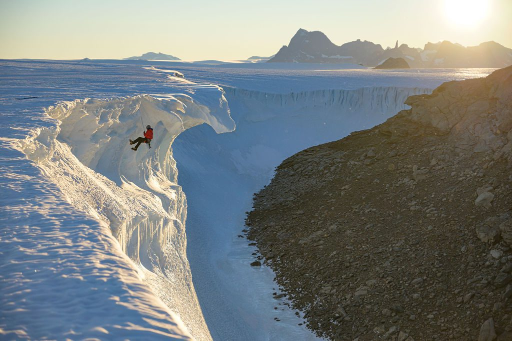 adventure guest abseiling off the ice cliffs in Antarctica