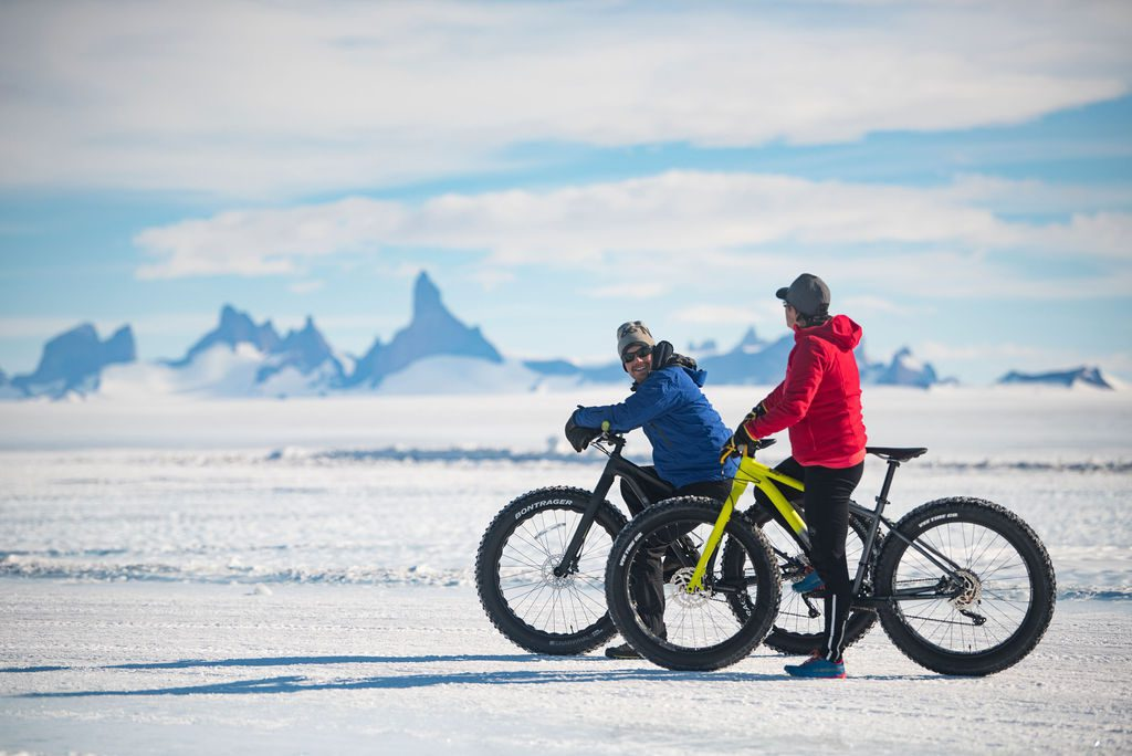 two guests enjoying fat tire bikes on the ice in Antarctica with jagged mountain peaks in the distance