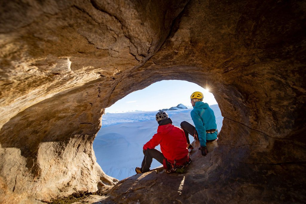 two hikers peaking though a round opening in the rocks of Antarctica